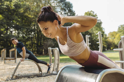 Woman doing push-ups on a fitness trail - MFF04822