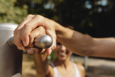 Close-up of man and woman holding a handle together on a fitness trail - MFF04834
