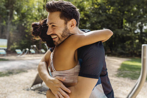 Man and woman hugging on a fitness trail - MFF04837