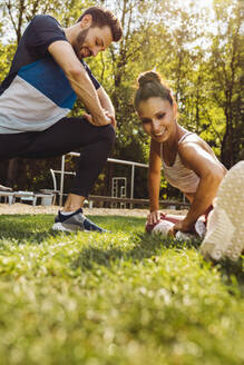 Man and woman stretching on grass near a fitness trail - MFF04840