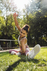 Woman stretching on grass near a fitness trail - MFF04843