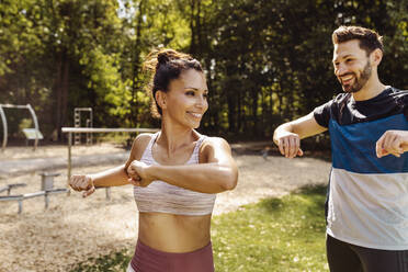 Man and woman stretching near a fitness trail - MFF04852
