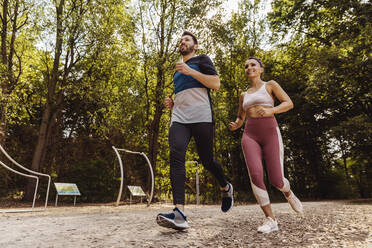 Sporty man and woman running near a fitness trail - MFF04858