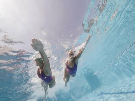 Two women swimming in a pool - OCMF00580