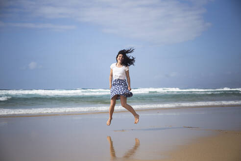 Laughing woman jumping in the air on the beach, Fuerteventura, Spain - ABZF02513
