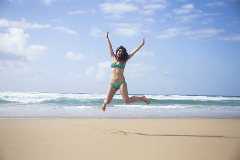Laughing woman jumping in the air on the beach, Fuerteventura, Spain - ABZF02519