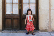 Portrait of smiling little girl with wooden toy camera wearing red dress with floral design - GEMF03111