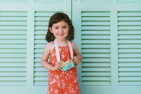 Portrait of smiling little girl with wooden toy camera - GEMF03117