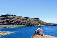Man sitting on cliff looking towards El Golfo beach, Lanzarote, Canary Islands, Spain - KIJF02626