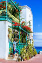 Man with hat next to house full of flowers, Lanzarote, Canary Islands, Spain - KIJF02629