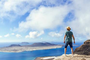 Man on viewpoint looking to La Gracioas island from Lanzarote, Canary Islands, Spain - KIJF02632