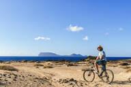 Man on a bicycle, La Graciosa island, Lanzarote, Canary Islands, Spain - KIJF02641