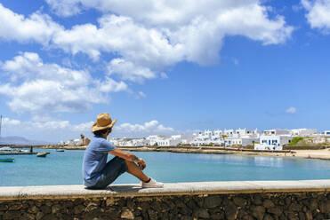 Man sitting on wall looking towards Caleta de Sebo, La Graciosa, Canary Islands, Spain - KIJF02644