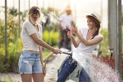 Two happy young women having fun while watering flowers with hose in the greenhouse - JSRF00556