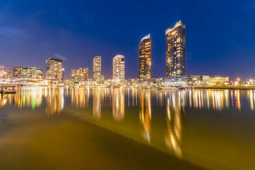 Illuminated buildings by Yarra River at Docklands against sky, Melbourne, Australia - SMAF01318