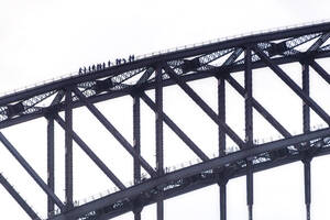 Silhouette people climbing Sydney Bridge against clear sky, Australia - SMAF01324