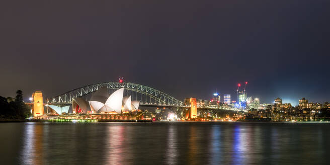 Illuminated Sydney Harbor Bridge and buildings over river against sky at night, Australia - SMA01327