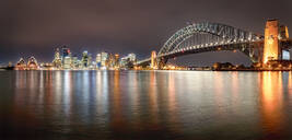 Panoramic shot of illuminated Sydney Harbor Bridge over river against sky at night - SMAF01330