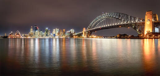 Panoramic shot of illuminated Sydney Harbor Bridge over river against sky at night, Sydney, Australia - SMAF01330