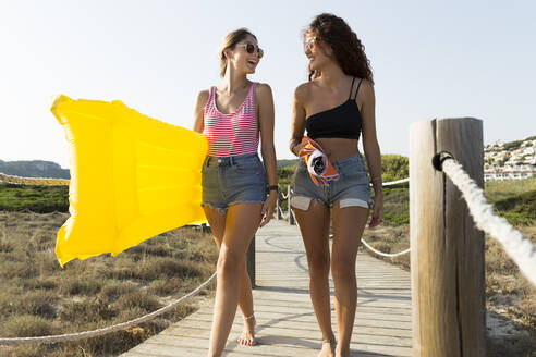 Young women with yellow airbed and sunshade walking to the beach - JPTF00249