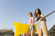 Young women with yellow airbed walking to the beach - JPTF00252