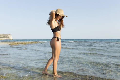 Young woman standing at the beach - JPTF00258