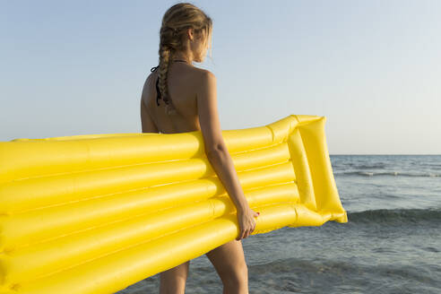 Rear view of young woman with yellow airbed at the beach, looking at distance - JPTF00267