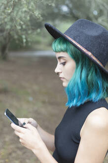Profile of young woman with dyed blue and green hair using smartphone on rainy day - JPTF00276