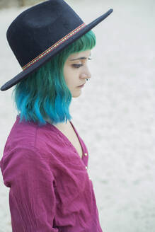 Portrait of young woman with dyed blue and green hair and nose piercing outdoors - JPTF00282