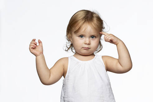 Portrait of blond girl tapping one's forehead, white background - VGF00276