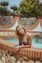 Portrait of a beautiful young woman wearing a bikini in a swimming pool - ACPF00604