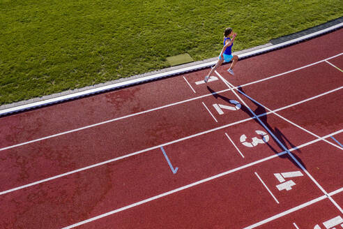 Aerial view of a running young female athlete on a tartan track crossing finishing line - STSF02197