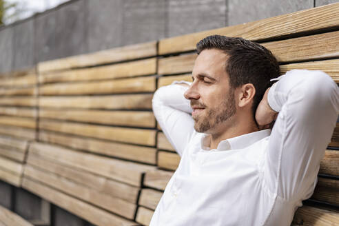 Relaxed businessman sitting on wooden bench in the city - DIGF08092