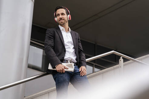 Businessman with headphones standing on stairs in the city - DIGF08131