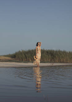 Beautiful woman in a summer dress standing at a lake - MOMF00747