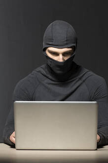 Masked hacker using laptop - VGF00282