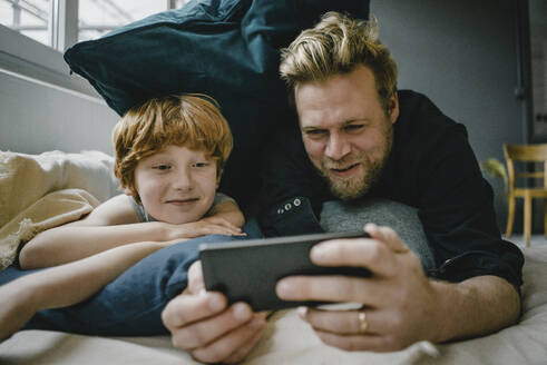 Portrait of father and son lying on couch looking at cell phone - KNSF06262