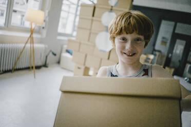 Portrait of smiling redheaded boy with cardboard box - KNSF06271