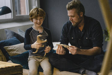 Portrait boy sitting with his father on couch kneading dinosaur - KNSF06286