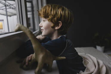 Sad boy leaning on window sill looking out of window in the evening - KNSF06289