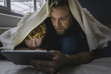 Father and son lying together under blanket looking at digital tablet - KNSF06292