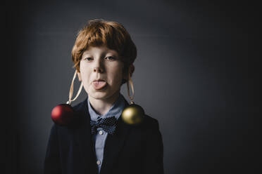 Portrait of redheaded boy wearing bow tie and Christmas baubles sticking out tongue - KNSF06304