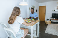 Couple having a meal in living room - KIJF02652