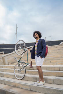 Stylish man with bicycle on stairs in the city - AFVF03845