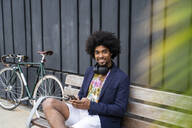Portrait of stylish man with cell phone sitting on a bench - AFVF03851