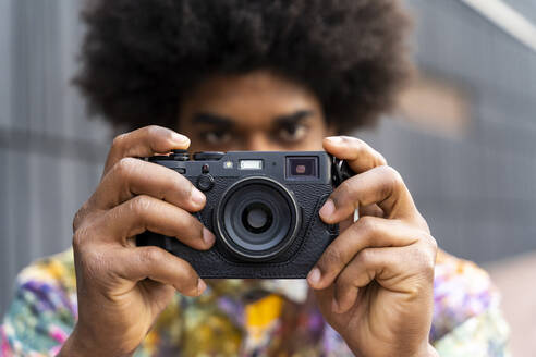 Close-up of man with a camera wearing colorful shirt - AFVF03872