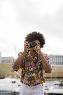 Man wearing colorful shirt taking pictures with a camera - AFVF03875