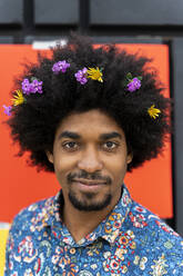 Portrait of man with blossoms in his hair wearing colorful shirt - AFVF03881