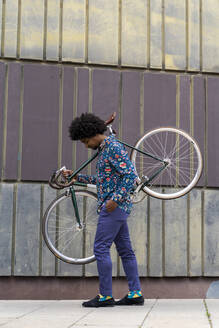 Stylish man carrying bicycle in the city - AFVF03887