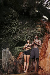 Couple practising yoga at waterfall, tree position - LJF00716